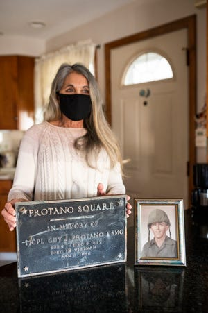 Dianne Protano shows off the recently damaged plaque from a monument to her brother Guy, who died in Vietnam, inside her family home on Solferino Street in Worcester. A nearby business has surveillance video of a truck running over the monument.