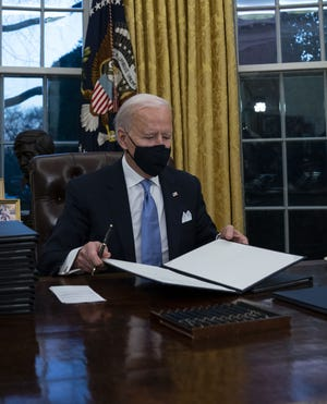 In this Jan. 20  file photo President Joe Biden signs a series of executive orders in the Oval Office of the White House in Washington.