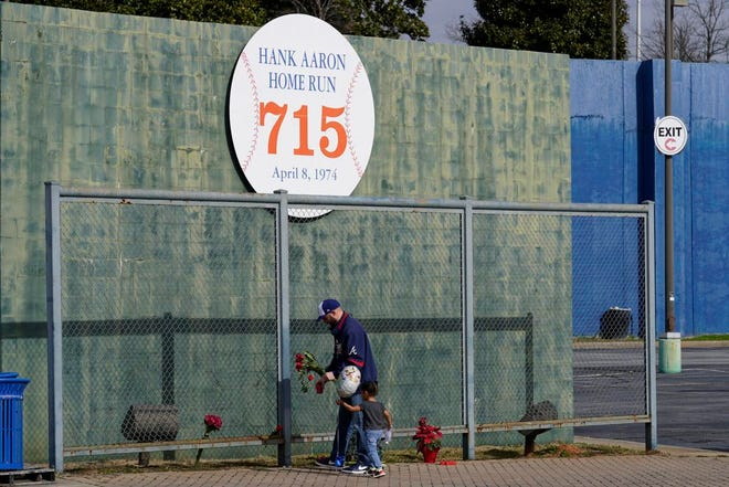 Les Motes and 2-year-old daughter Mahalia leave flowers Friday near the spot where Hank Aaron's 715th home run cleared the fence in left field in 1974.