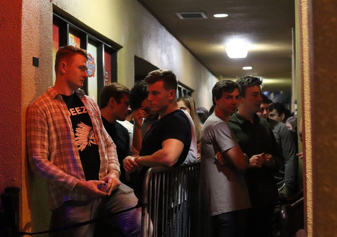 Bar-goers wait in line to enter Fat Daddy's at Midtown in Gainesville on Friday.