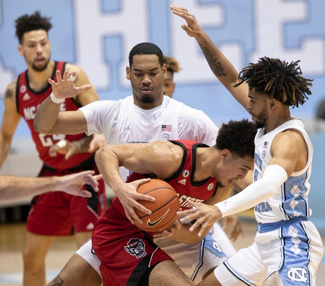 North Carolina's Garrison Brooks and RJ Davis, right, catch N.C. State's Jericole Hellems in a trap during Saturday afternoon's game at the Smith Center.