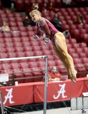 Mati Waligora competes on the bars as Alabama gymnasts defeated Auburn Friday, Jan. 22, 2021. [Staff Photo/Gary Cosby Jr.]