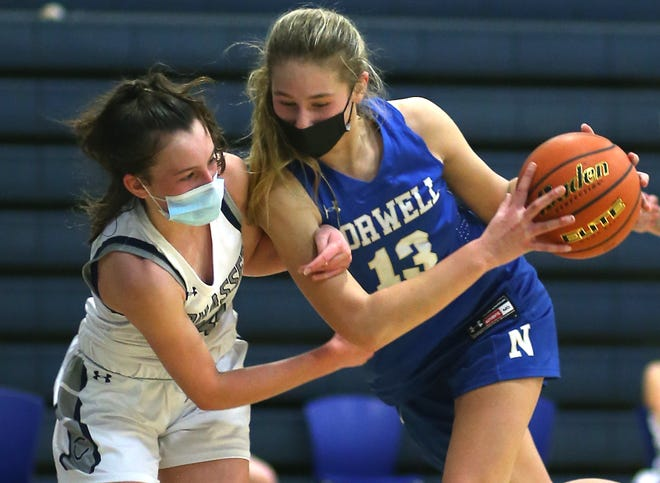 Norwell's Grace Oliver is fouled by Cohasset's Sarah Chenette while battling for the rebound during third quarter action of their game at Cohasset High on Friday, Jan. 22, 2021.
