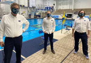 Michigan swimming and diving coaches, including Mike Bottom, left, wear Michigan State masks during Friday's meet.