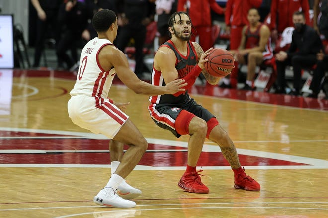 Ohio State's Duane Washington eyes the rim in with Wisconsin's  by D'Mitrik Trice closing in on defense Saturday at the Kohl Center.