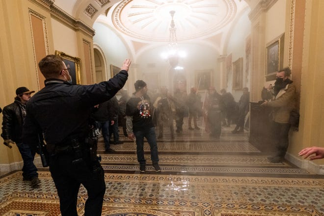 FILE - In this Wednesday, Jan. 6, 2021 file photo smoke fills the walkway outside the Senate Chamber as supporters of President Donald Trump are confronted by U.S. Capitol Police officers inside the Capitol in Washington. Kevin Strong, a Federal Aviation Administration employee and QAnon follower from California who had been on the FBI's radar is facing federal charges after authorities say he confessed to taking part in the siege of the U.S. Capitol. (AP Photo/Manuel Balce Ceneta, File)