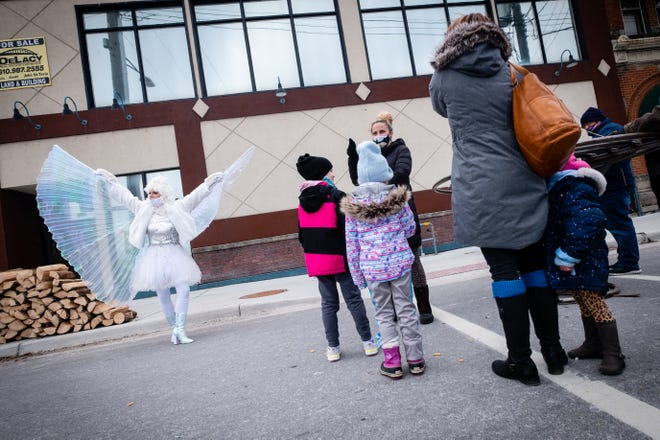 Dressed as a winter fairy, Michelle Wolford, from Wonder Wolf Entertainment, left, shows off her sparkly wings to Reagan Smith, her sister Parker, and several others during Winter Wonderland Saturday, Jan. 23, 2021, in downtown Port Huron.