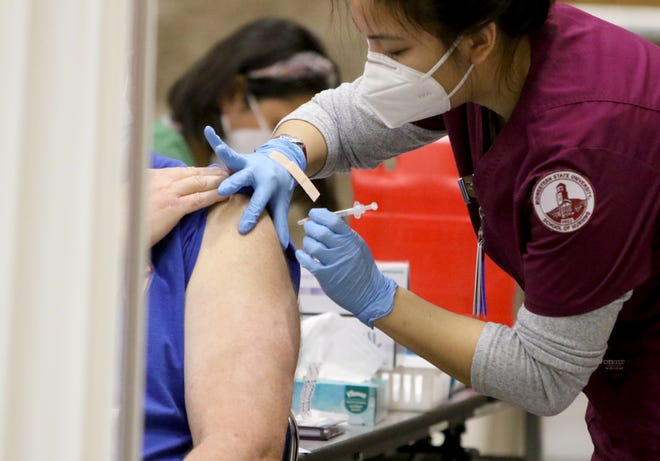 A Midwestern State University nursing student gives a man the Covid-19 vaccine at the Wichita Falls-Wichita County Public Health District vaccination clinic Saturday, Jan. 23, 2021, in the Ray Clymer Exhibit Hall at the MPEC.