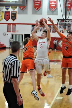 Sheridan's Shay Taylor puts up a shot over Meadowbrook's Drew Webster (00) and Davis Singleton (10) in Friday's game. The Generals won 64-44.