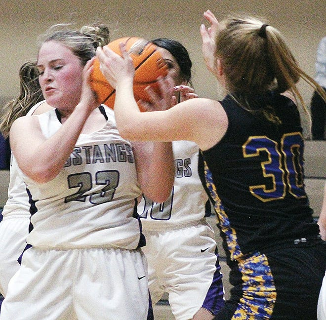 Wesleyan Christian School's Rachel Hopkins, left, gets a firm grip on the basketball during girls' action Friday in Bartlesville.