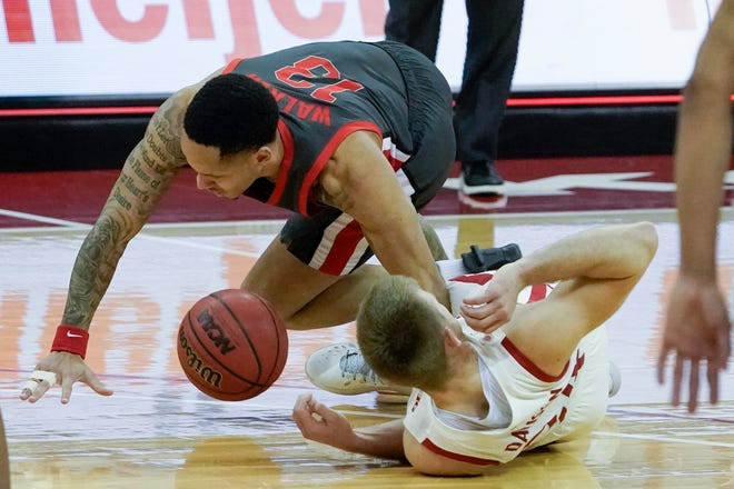 Ohio State guard CJ Walker, top, tangles with Wisconsin's Brad Davison while going for a loose ball in the OSU senior's return to action in Saturday's win in Madison, Wis.