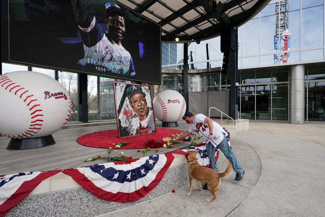 A man places flowers next to a portrait of Hank Aaron outside Truist Park in Atlanta on Friday.