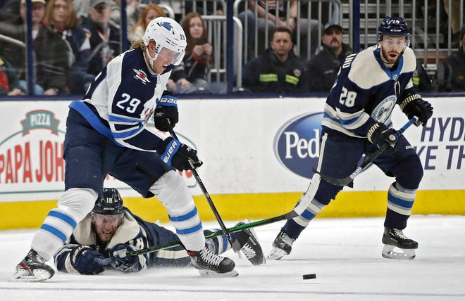 Patrik Laine, left, of the Jets, scrambles for the puck against Pierre-Luc Dubois, bottom, and Oliver Bjorkstrand of the Blue Jackets in a game last season. Laine and Dubois were part of a major trade between the teams on Saturday.