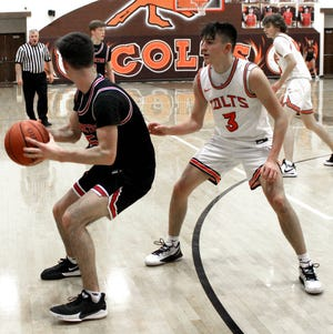 Meadowbrook junior  Jake Singleton (3) applies defensive pressure to Coshocton's Tucker Nelson (5) during Saturday afternoon's Muskingum Vallly League game at Meadowbrook High School. Singleton tallied a game-high 32 points to lead the Colts to a 69-43 victory.