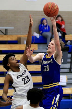Nickerson's Matt Crossman (33) shoots past Sunrise Christian Academy's Darius Hart (23) during their championship game Saturday night at the St. John Mid-Winter Classic Basketball tournament. Crossman scored 9 points in the game. Sunrise defeated Nickerson 53-35.