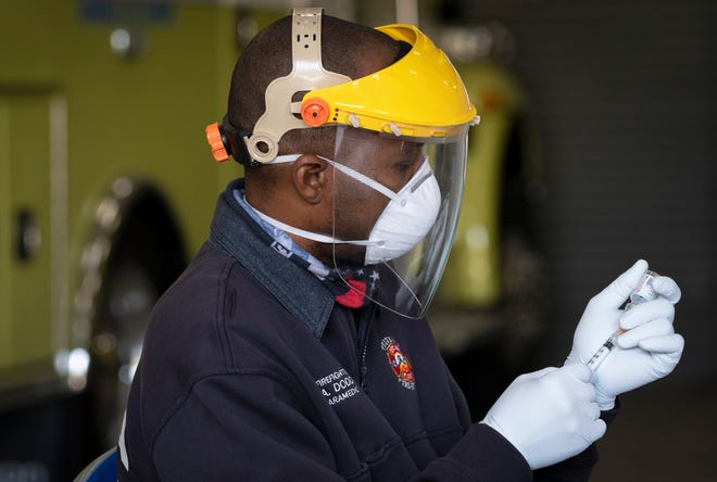 Firefighter/paramedic Andre Dodd prepares a shot of the Moderna COVID-19 vaccination at the Tequesta Fire Department on Jan. 15.