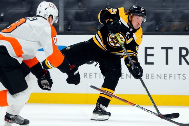 Bruins forward Brad Marchand, defended by the Philadelphia Flyers' Robert Hagg, takes a shot during the second period of Saturday night's game in Boston.