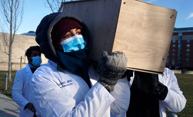Dr. Elizabeth Samuels, an assistant professor of emergency medicine at Brown Medical School, hoists a mock casket on her shoulders as she joins other medical professionals in a procession at Sunday's candlelight vigil of remembrance in Providence.