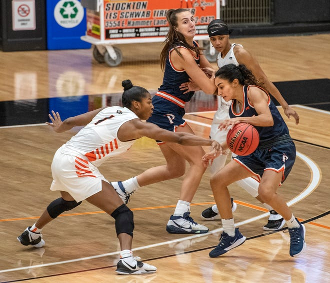 University of the Pacific's Brooklyn McDavid slaps the ball away from a Pepperdine player at Spanos Center on Saturday.