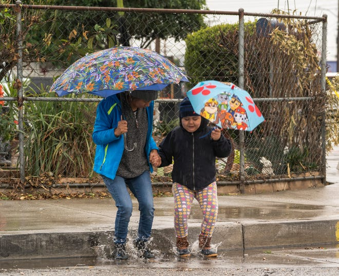Mariella Velazquez plays with her daughter Elisa Medina, 11, in El Monte on Saturday. Rain and snow is falling as the first in a series of storms moves through California in a major change toward real winter weather.