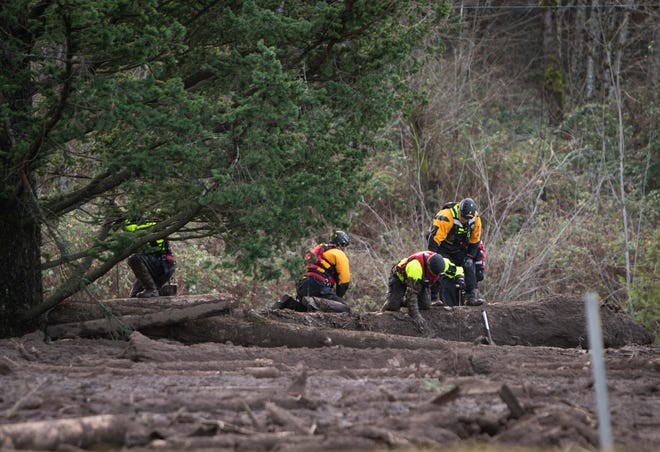 Search and rescue crews use metal rods to poke through the mud Jan. 14 as they continue to search for a missing woman whose car was swept away by a landslide Wednesday in the Dodson area of the Columbia River Gorge, in Oregon. Sheriff's deputies and firefighters on Saturday, Jan. 23 recovered the body of an Oregon woman whose vehicle was swept away in a deep mudslide during a winter storm last week.