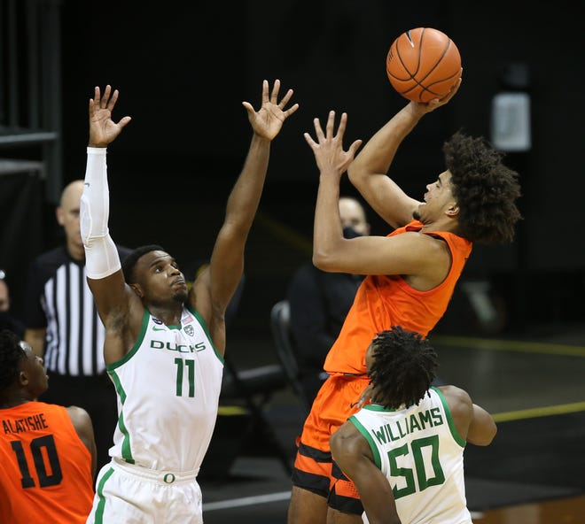 Oregon State's Ethan Thompson, center, shoots over Oregon's Amauri Hardy, left, and Eric Williams Jr. during the second half.