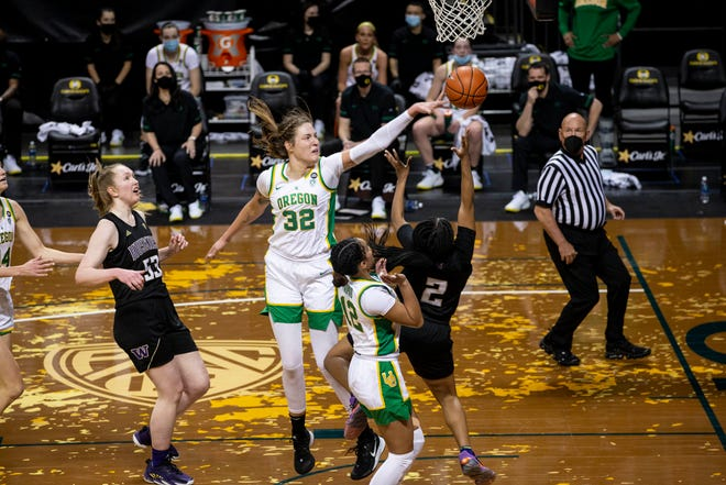 UO Sedona Prince (32) swats the ball from UW Tameiya Sadler (2) lay up in the game against University of Washington at Matthew Knight Arena on Sunday, Jan. 24, 2021.
