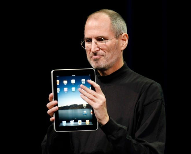 In this Jan. 27, 2010, photo, Apple CEO Steve Jobs shows off the new iPad during an event in San Francisco.