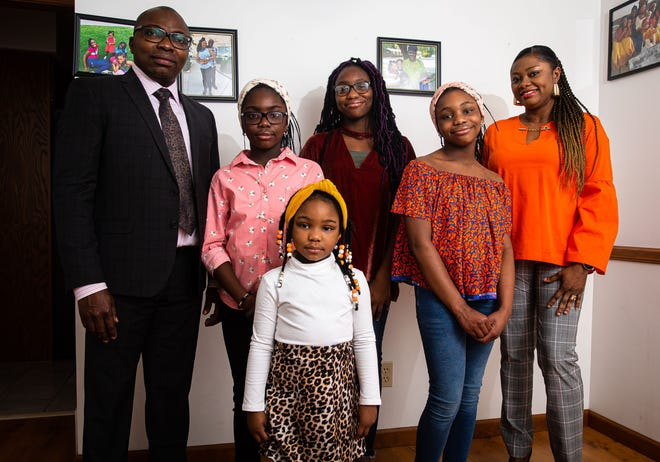 Dr. Francis Abiola Oka, left, along with his daughters Frances Adedoyin Oke, 7, Kathrine Adedayo Oke, 4, Josephine Ayodeji Oke, 12, Beatrice Ajibola Oke, 8, and his wife Abimbola Joy Oke, right, received a phone call from then-President-elect Joe Biden that lasted for 20 minutes along with his daughters also getting to speak with First Lady Jill Biden. [Justin L. Fowler/The State Journal-Register]