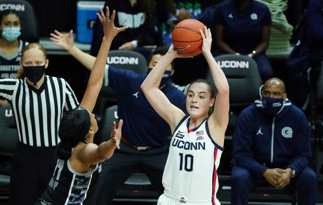 Connecticut guard Nika Muhl (10) looks to pass against Georgetown forward Jillian Archer (14) in the first half of an NCAA college basketball game Saturday, Jan. 23, 2021, in Storrs.