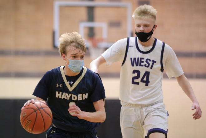 Hayden sophomore Jake Muller dribbles down court against Topeka West junior Zander Putthoff in the first half of Saturday's game in the Topeka Invitational Tournament at Topeka High.