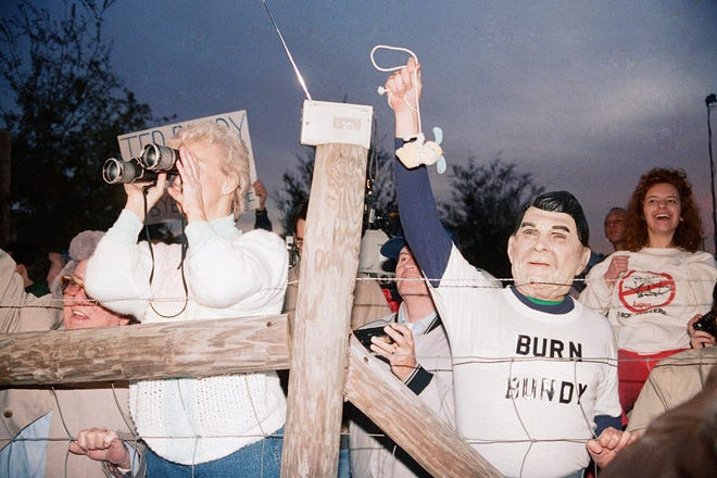 A toy bunny is hung in effigy by Jerry Jackson of Atlanta Ga., wearing a Ronald Reagan mask, and the pro-death penalty crowd rejoices after the Theodore Bundy execution, Jan. 25, 1989 at sunrise in Starke, Fla.