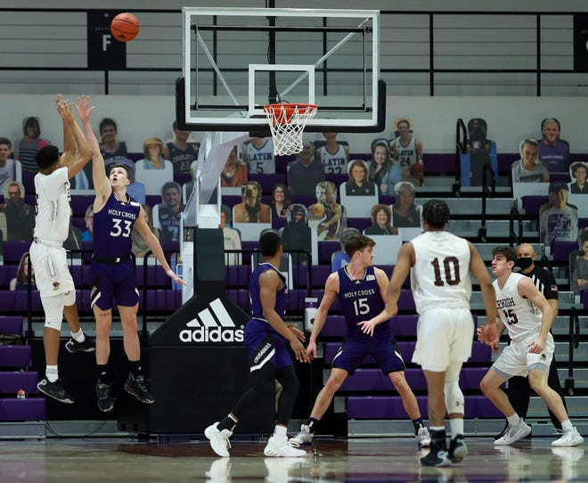 Holy Cross' Judson Martindale attempts to block as Lehigh's Evan Taylor makes a shot.