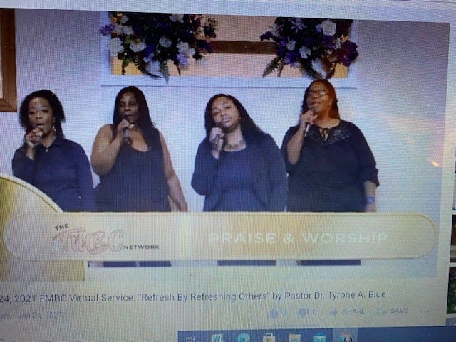 Members of the First Missionary Baptist Church Praise Team lead praise and worship during the church's Sunday morning worship service broadcast via YouTube.