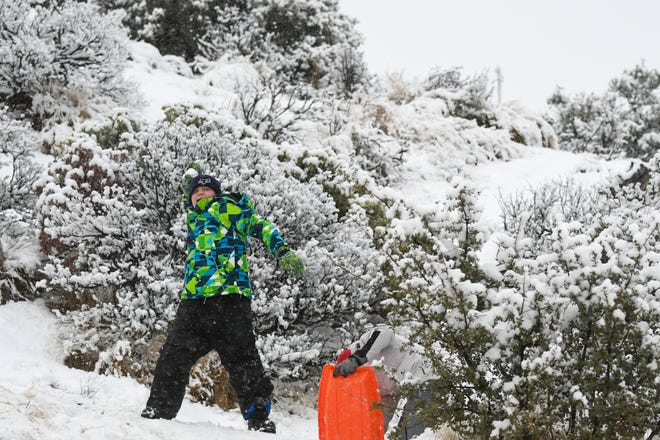 Mason Dominiak, of Lancaster, tosses a snow ball while playing with his family at the intersection of highways 138 and 2, about 11 miles from Wrightwood, Calif.