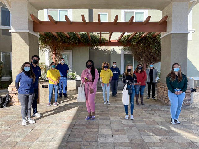 Two Victor Valley College students, center, stand with members of Searchlight Society and others after being temporarily housed through a new program on Jan. 18, 2021.
