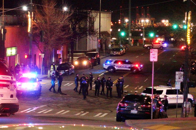 Tacoma Police and other law enforcement officers stand in an intersection near the site of a car crash Saturday, Jan. 23, 2021, in downtown Tacoma. At least one person was injured when a police car plowed through a crowd of people Saturday night who were watching a downtown street race, the Tacoma News-Tribune reported.