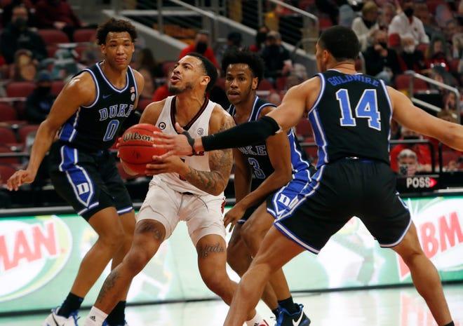 Louisville's Carlik Jones draws attention from three of Duke's players. 01/23/21