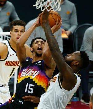Jan 23, 2021; Phoenix, Arizona, USA; Suns' Cameron Payne (15) draws a foul against Nuggets' JaMychal Green (0) during the first half at the Phoenix Suns Arena. Mandatory Credit: Patrick Breen-Arizona Republic