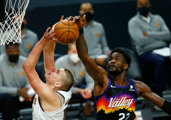 Jan 23, 2021; Phoenix, Arizona, USA; Suns' Deandre Ayton (22) blocks a shot from Nuggets' Nikola Jokic (15) during the second half at the Phoenix Suns Arena. Mandatory Credit: Patrick Breen-Arizona Republic