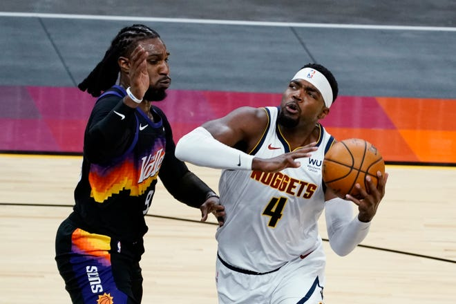 Denver Nuggets forward Paul Millsap (4) drives on Phoenix Suns forward Jae Crowder during the first half of an NBA basketball game Saturday, Jan. 23, 2021, in Phoenix. (AP Photo/Rick Scuteri).