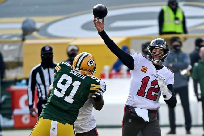 Jan 24, 2021; Green Bay, Wisconsin, USA; Tampa Bay Buccaneers quarterback Tom Brady (12) throws a pass against Green Bay Packers outside linebacker Preston Smith (91) during the first quarter in the NFC Championship Game at Lambeau Field . Mandatory Credit: Benny Sieu-USA TODAY Sports