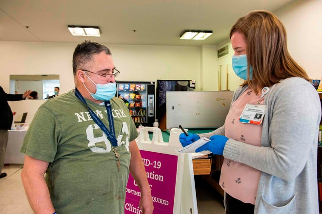 William Torres, 56, a resident of The Open Hearth mens shelter, prepares to receive the Pfizer-BioNTech Covid-19 vaccine from a Mobile Vaccination Clinic run by Hartford HealthCare in Hartford, Connecticut, on Jan. 22, 2021.