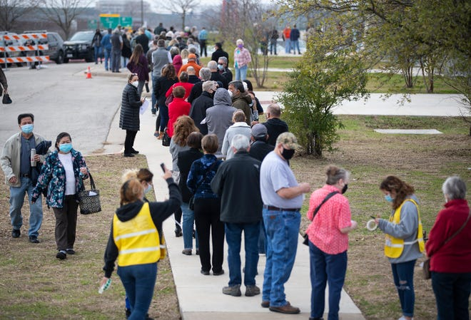 Hundreds of people who made an appointment to be vaccinated against COVID-19 stand in a line that wraps around a building at the Delco Activity Center in northeast Austin, Texas, on Jan. 23.