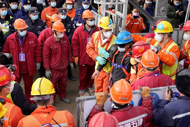 A miner is pulled to safety on Sunday in Qixia in eastern China's Shandong province after an explosion trapped the crew for two weeks.