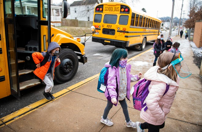 Northside School students get off the bus and enter the building Monday morning for the first day of in-person classes this year in Ellwood City. [Lucy Schaly/For BCT]
