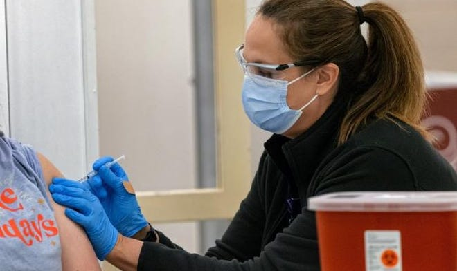 A nurse administers an injection of the COVID-19 vaccine recently in Norman.