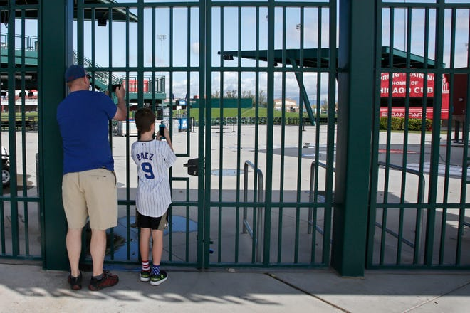 Fans take photos last March through locked gates at Sloan Park in Mesa, Ariz., the spring training site of the Chicago Cubs.