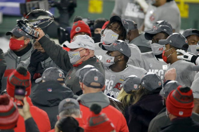 Buccaneers head coach Bruce Arians holds the trophy after winning the NFC championship against the Packers on Sunday.