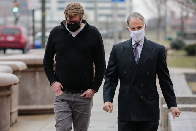 Dustin Thompson, left, of Columbus, who is accused of being part of the Jan. 6, 2021 insurrection at the U.S. Capitol, arrives with his lawyer, Sam Shamansky, to turn himself in on Monday, Jan. 25, 2021 at the Joseph P. Kinneary U.S. District Courthouse in Columbus, Ohio. Thompson is accused of entering the Capitol and stealing a coat rack from inside.